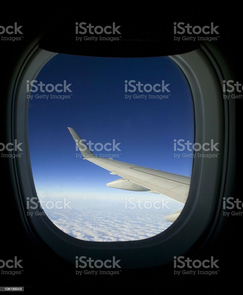 Looking Out of Airplane Window at Wing Above Clouds royalty-free stock photo