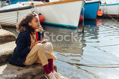 A young girl sitting on steps at a commercial dock while on vacation in Polperro, Cornwall. She is holding a mobile phone while looking off into the distance.