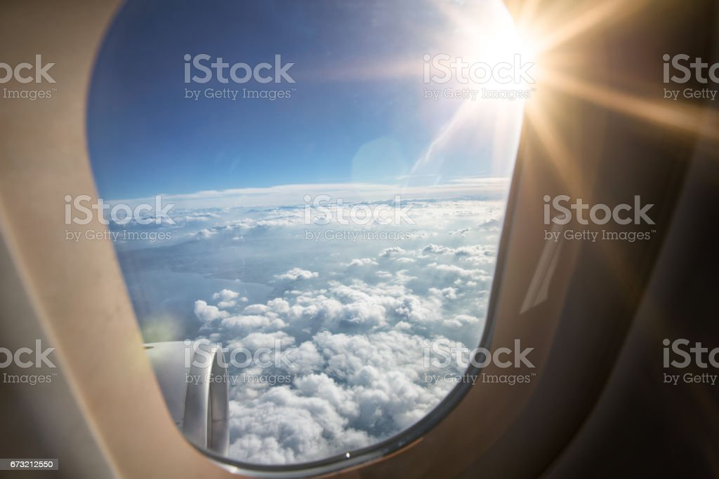 Looking outside of airplane window into bright sunlight beam stock photo