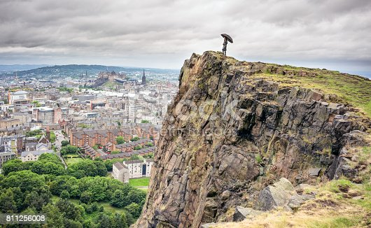 A woman standing above Salisbury Crags, in Holyrood Park, holding an umbrella for shelter as she looks over the city of Edinburgh.