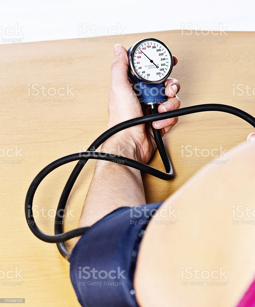 Looking over shoulder of woman taking own blood pressure reading royalty-free stock photo