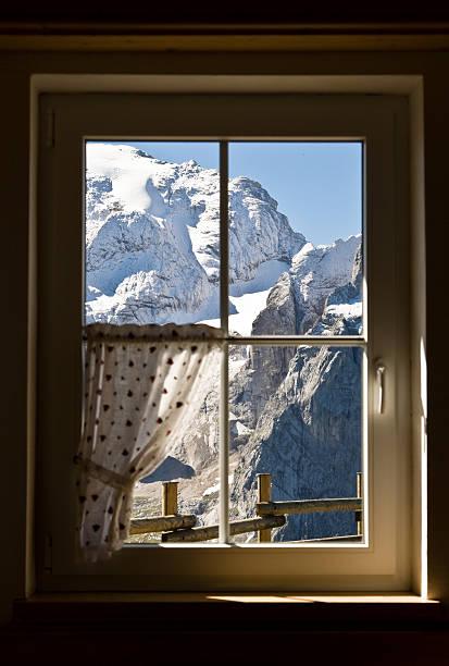 blick auf die schneebedeckten berge durch fenster - hotel alpenblick stock-fotos und bilder