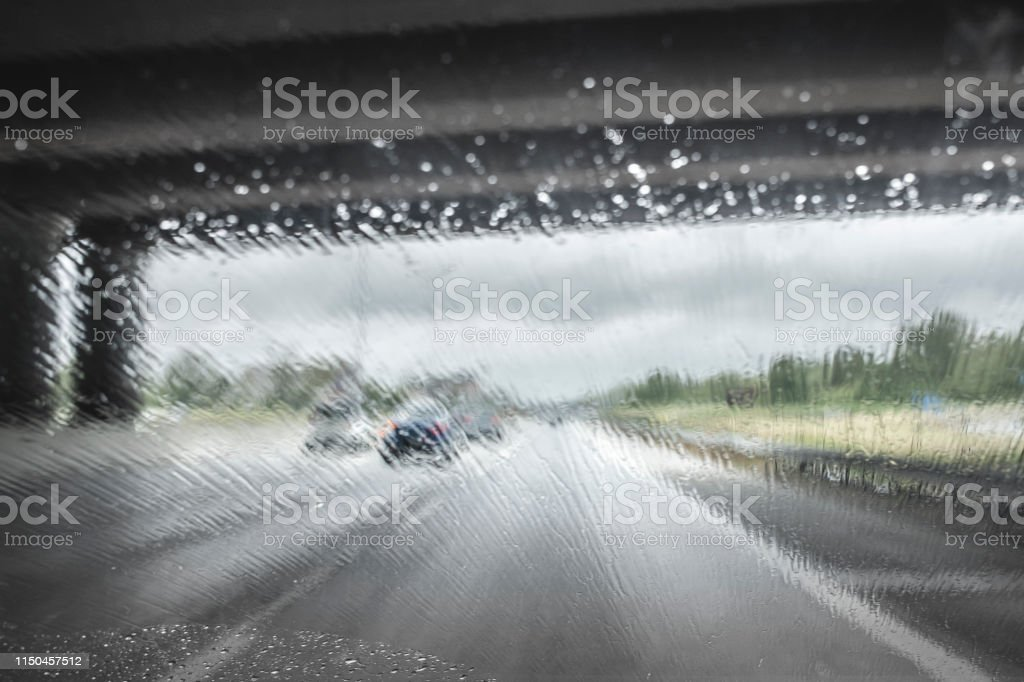 Driving with bad weather on the highway, rain on the car windshield