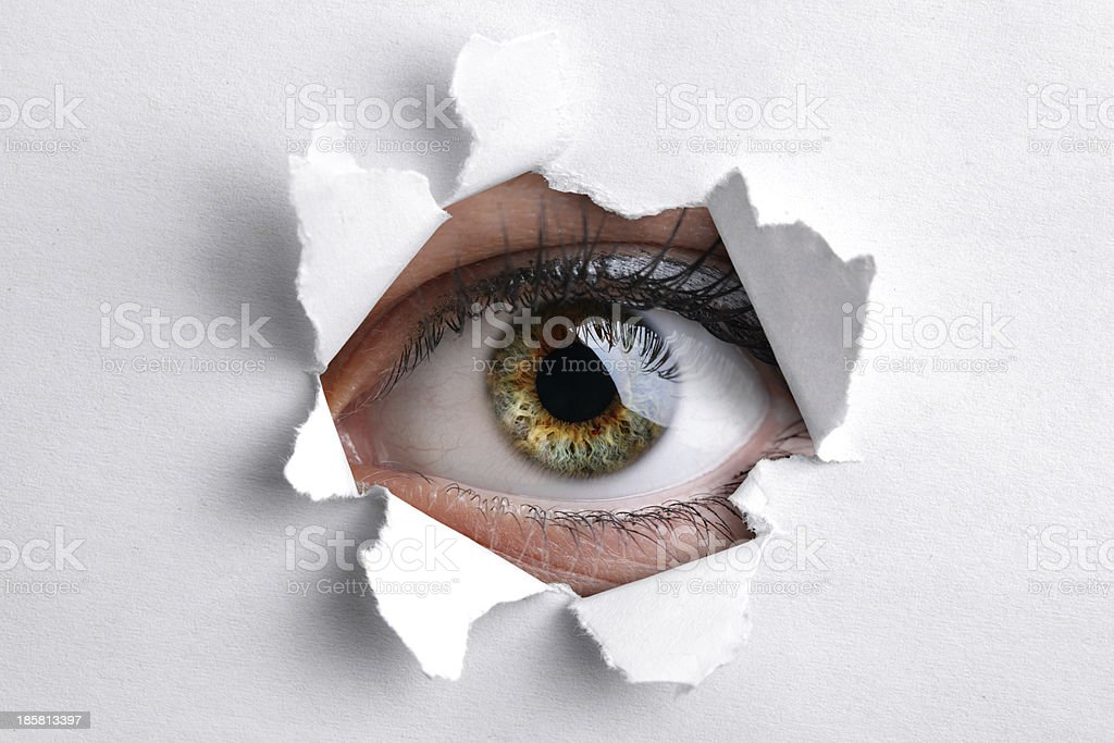 Looking through a hole in white paper stock photo