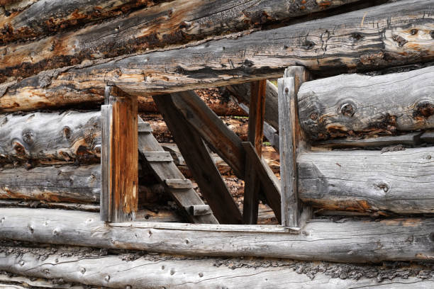 Looking through a window of an abandoned log cabin. stock photo