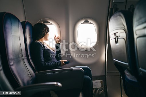 Young woman is looking through a window during airplane ride