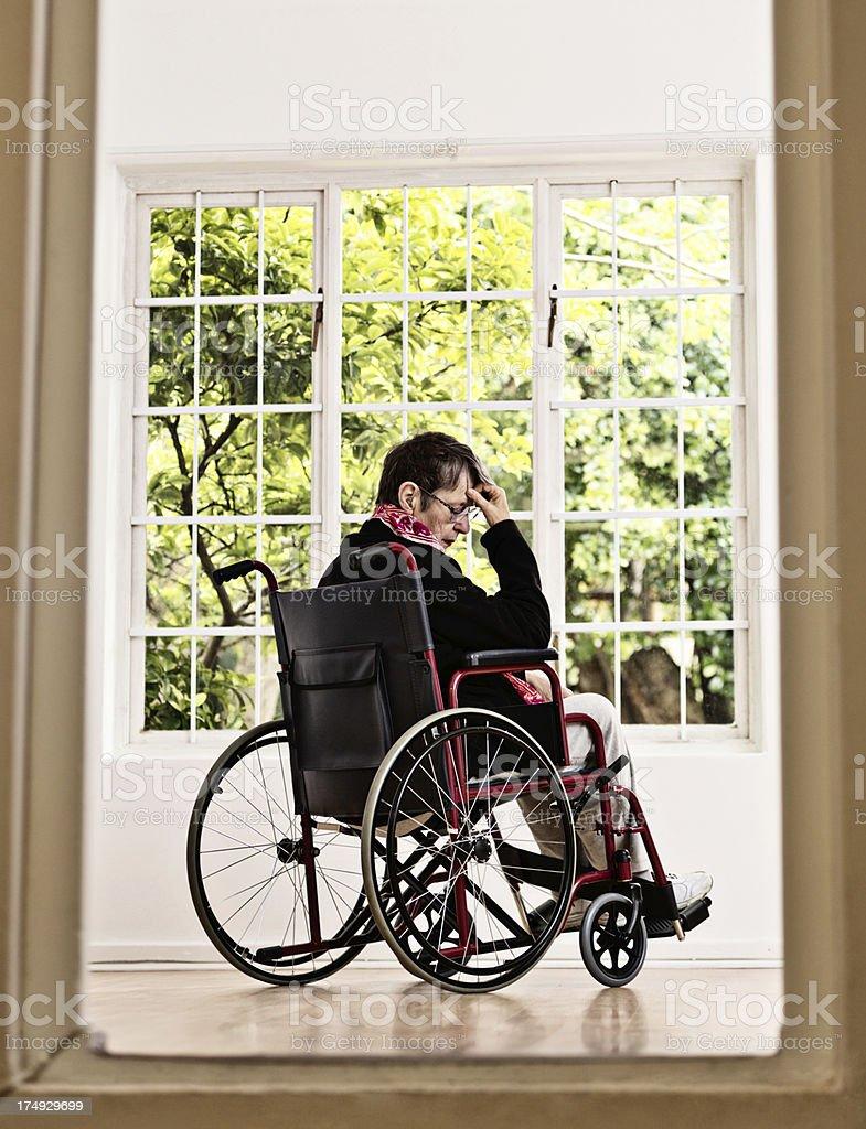 Looking through doorway at depressed old woman in wheelchair royalty-free stock photo