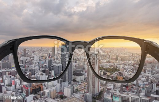 istock Looking through eyeglasses to city sunset view, focused on lens with blurry background 1144469499