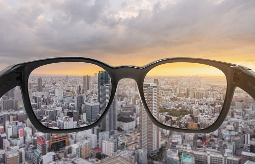 Looking through eyeglasses to city sunset view, focused on lens with blurry background
