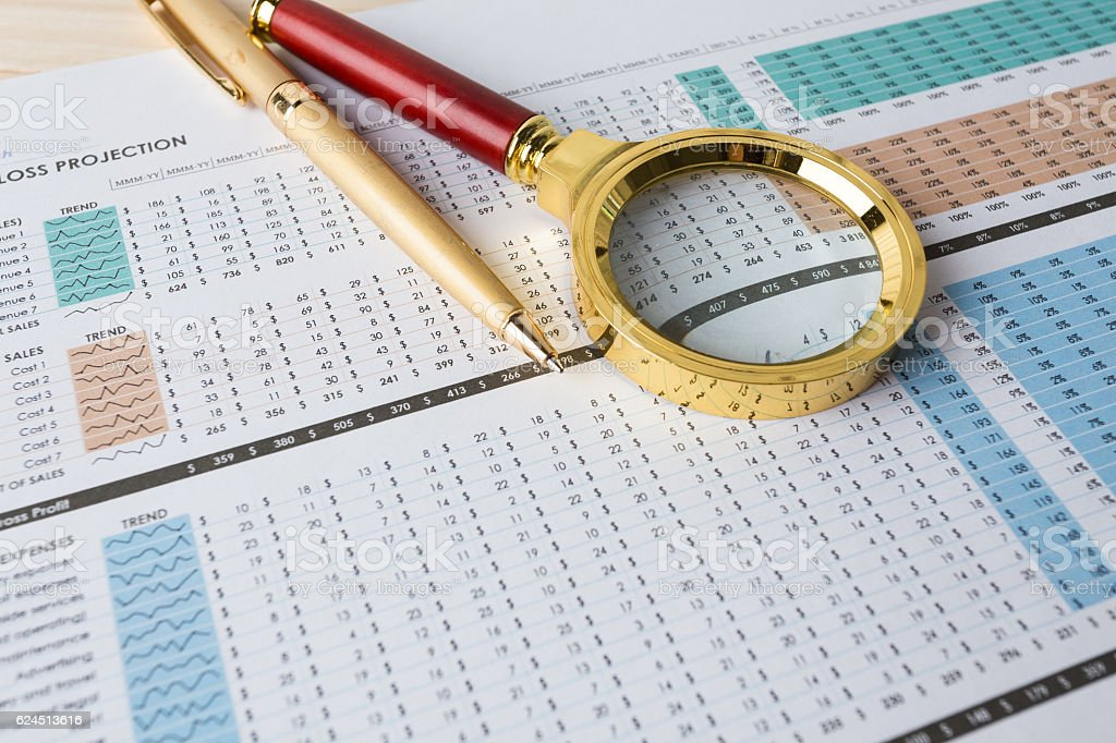 Looking through magnifying glass to financial report stock photo