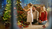 Looking Through Snowy Window. Happy Family: Father, Mother and Their Little Daughter are Decorating Christmas Tree.