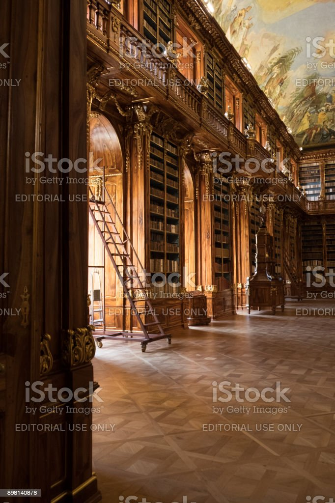Looking through the doorway into Theological Hall, Library of the Strahov Monastery in Prague, sun coming in through window. stock photo