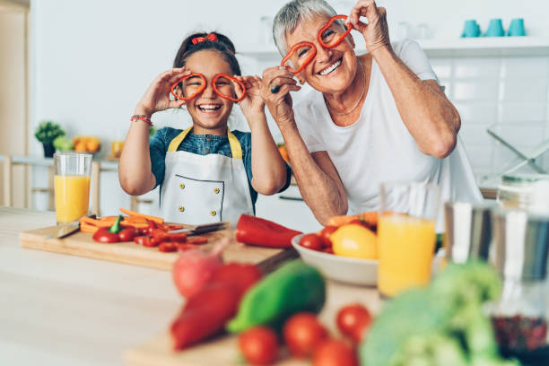 Looking through the happy glasses Playful grandmother and granddaughter in the kitchen young at heart stock pictures, royalty-free photos & images