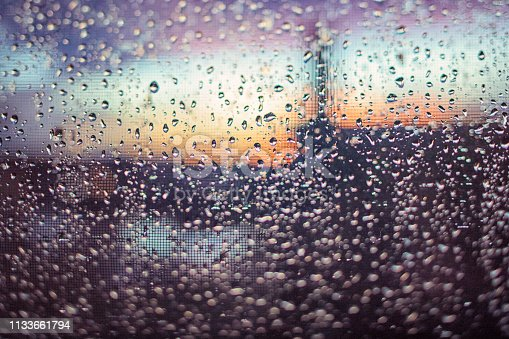 Looking through the window with fly screen after the rain in sunset