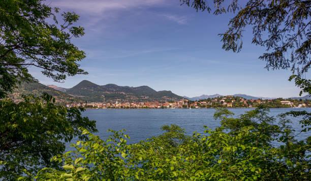 Looking through trees across a lake to a pretty Italian town stock photo