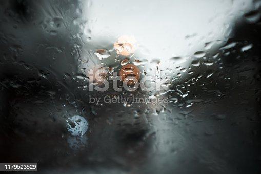 Brake lights seen through wet windscreen during rainstorm.