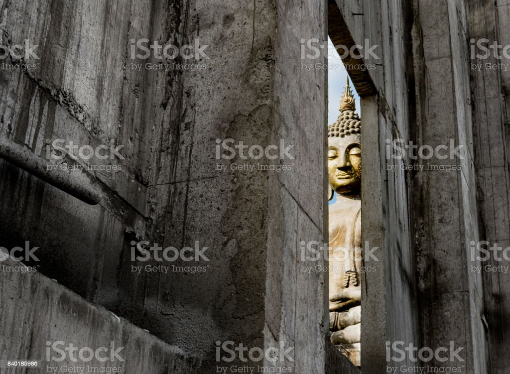 Looking through window at construction temple to see golden buddha statue stock photo