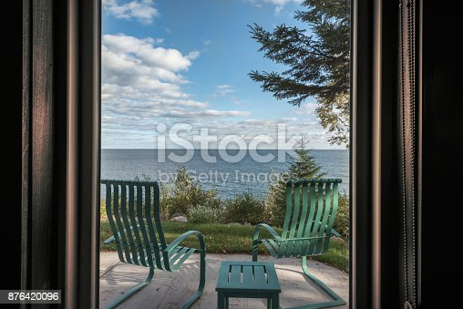 876420064istockphoto Looking through window at shore line with Chairs and Table 876420096