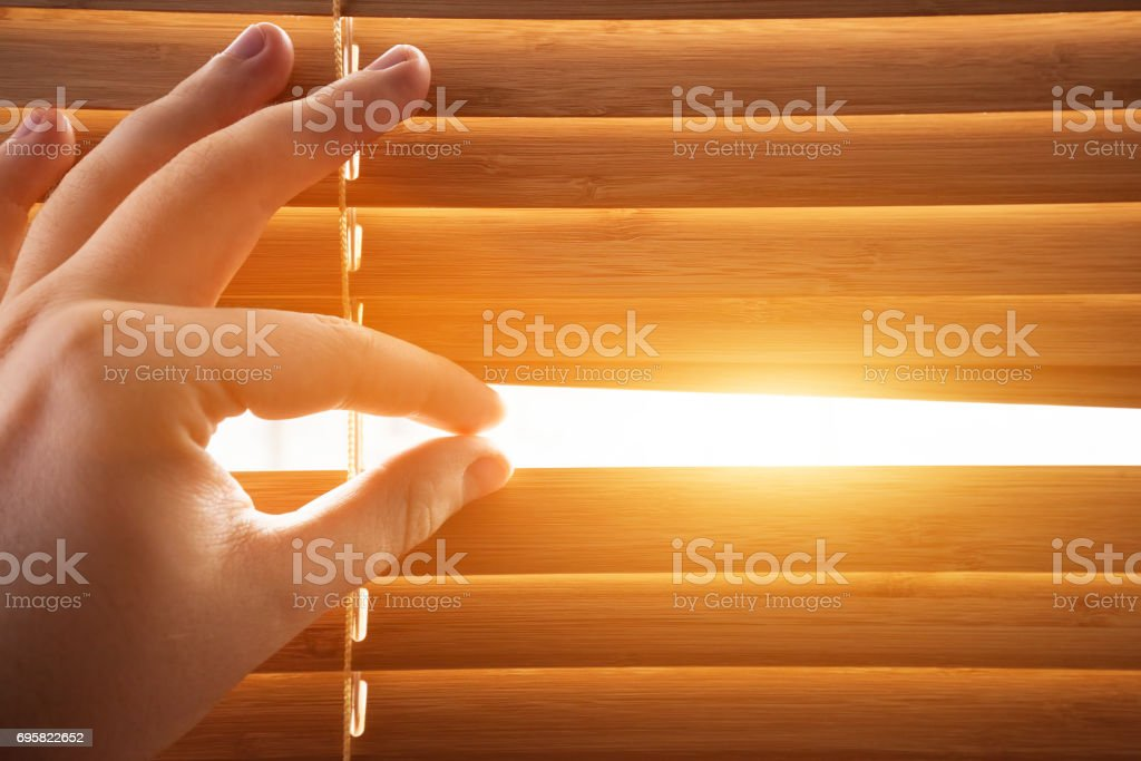 Looking through window blinds, sun light coming inside. – zdjęcie