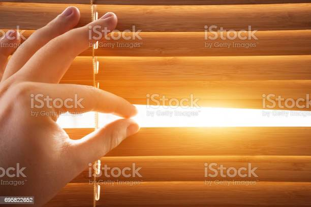 Photo of Looking through window blinds, sun light coming inside.
