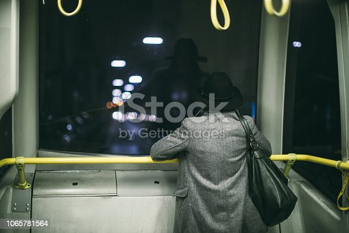 Rear view of woman watching through window in the bus at night
