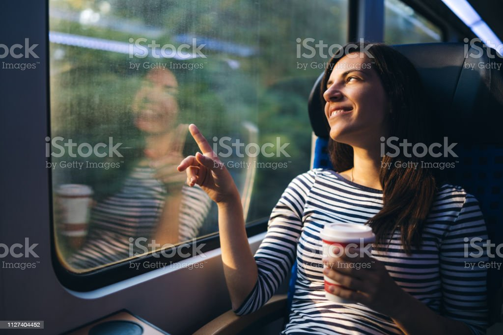 Young woman is admiring the view from in a train window