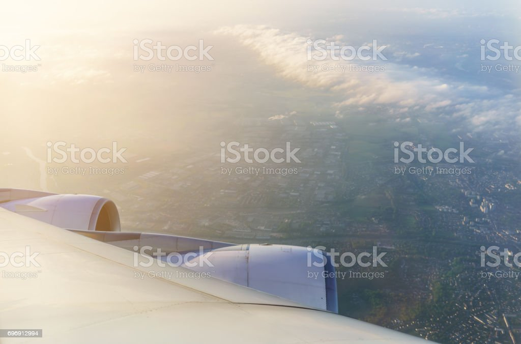 Looking thru airplane 's window in the morning seeing wing of airplane , white clouds and The City of Paris stock photo