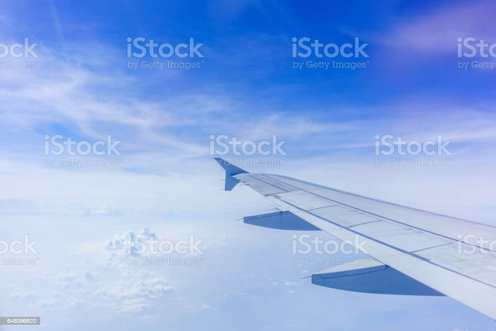 Looking thru airplane 's window seeing wing of airplane , white clouds and blue sky stock photo