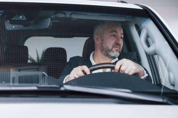 Blick zur Seite. Frontansicht des leitenden Geschäftsmannes in seinem neuen, modernen Auto testet neue Funktionen – Foto