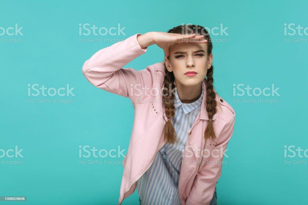 auf der Suche zu weit. Porträt von schönen niedlichen Mädchen stehend mit Make-up und braunen Zopf Frisur in gestreiften hellblaues Hemd rosa Jacke. – Foto