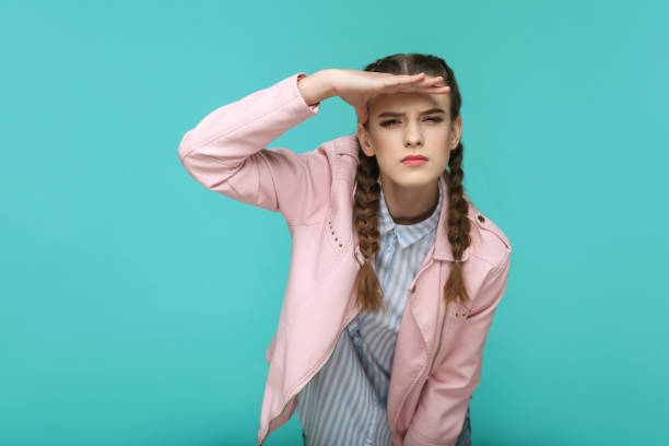 looking too far. portrait of beautiful cute girl standing with makeup and brown pigtail hairstyle in striped light blue shirt pink jacket. - searching stock pictures, royalty-free photos & images