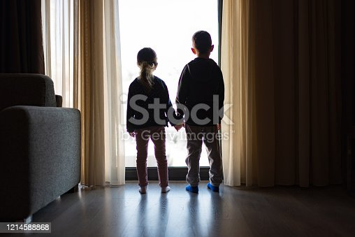 Boy and girl from back, looking trough the window.