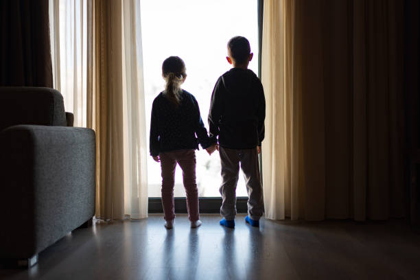Looking trough the window Boy and girl from back, looking trough the window. brother stock pictures, royalty-free photos & images