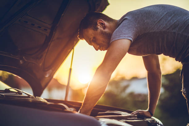 Looking under car hood Young man repairing car on the side of the road vehicle hood stock pictures, royalty-free photos & images