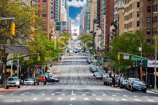 Manhattan, New York, USA - May 3, 2020: Street view looking up town 2nd Avenue with very little Traffic and Roosevelt Island Tram in background.