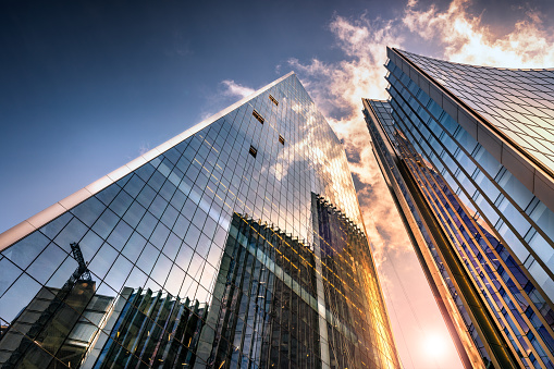 Low angle view of tall corporate glass skyscrapers reflecting a blue sky with white clouds