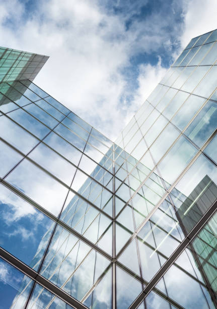 looking up a reflections on glass covered corporate building - vertical stock pictures, royalty-free photos & images