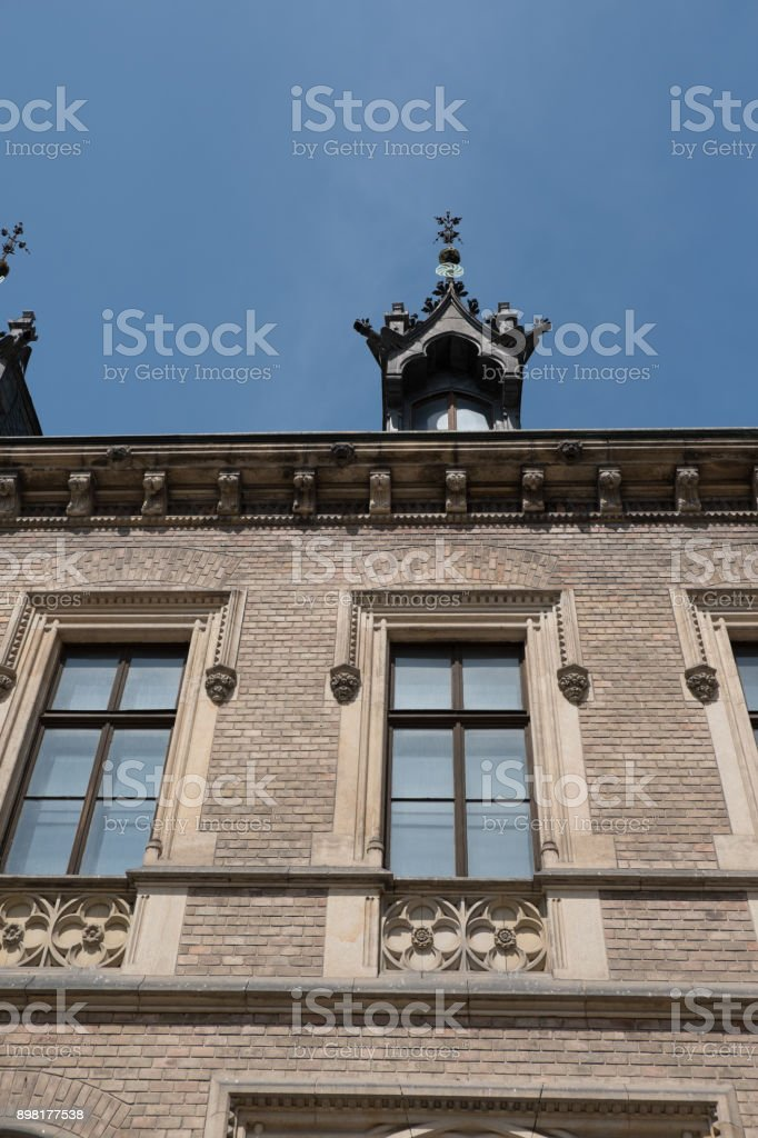 Looking up at a crenelated arch above a dormer window on the roof of the New Provost's Lodging building near Prague Castle in Prague, Czech Republic.  Carved dentils and quatrefoil on the facade. stock photo
