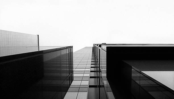 Looking up at a glass skyscraper Perspective looking up at a modern skyscraper monochrome stock pictures, royalty-free photos & images