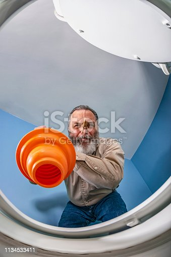 Looking up from inside the toilet bowl at an adult Caucasian male with a clothes pin on his nose using an orange accordion type toilet plunger to clear a clogged toilet at home.