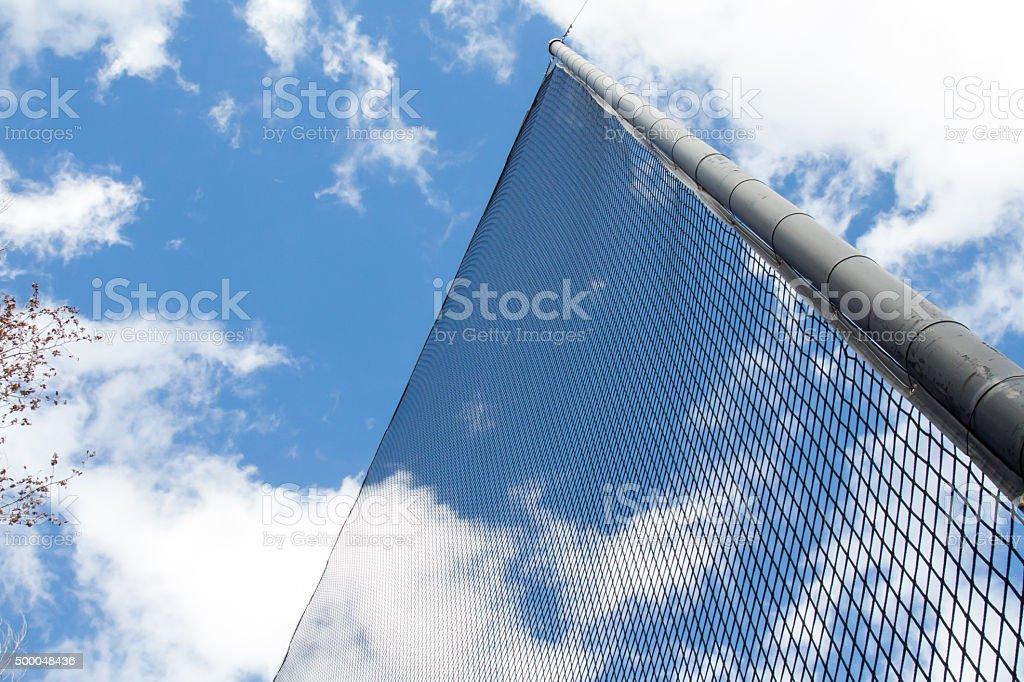 Looking up at a net at a baseball field stock photo