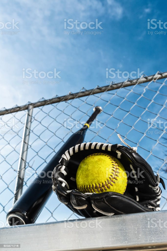 Looking up at a yellow softball in black glove and bat on bench stock photo