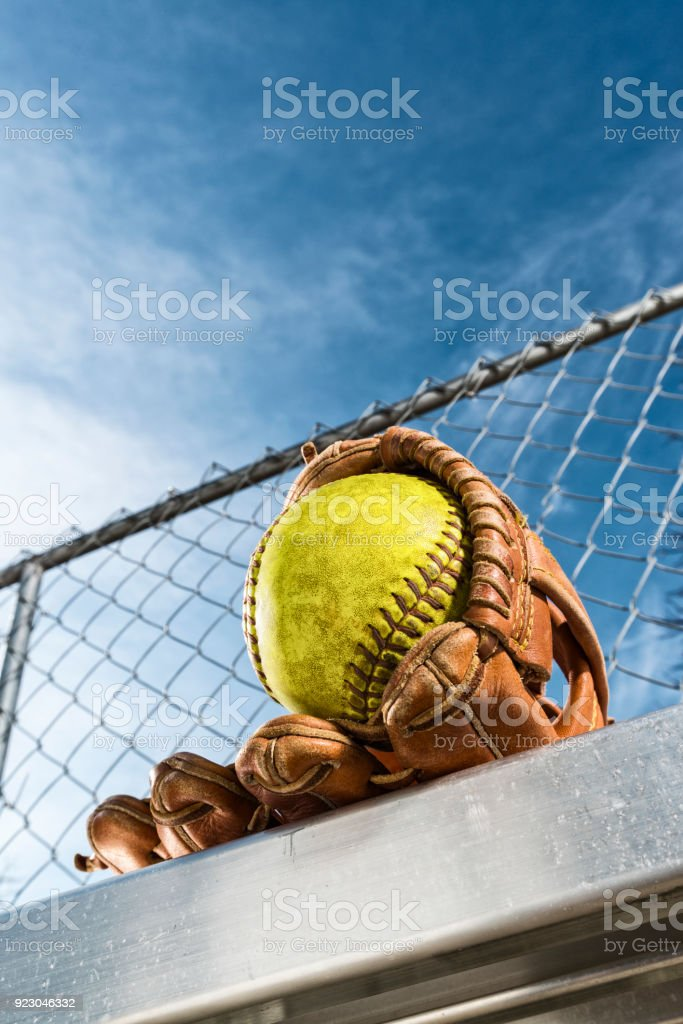 Looking up at a yellow softball in glove on bench stock photo
