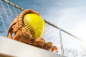 Looking up at a yellow softball in glove on bench with sun flare