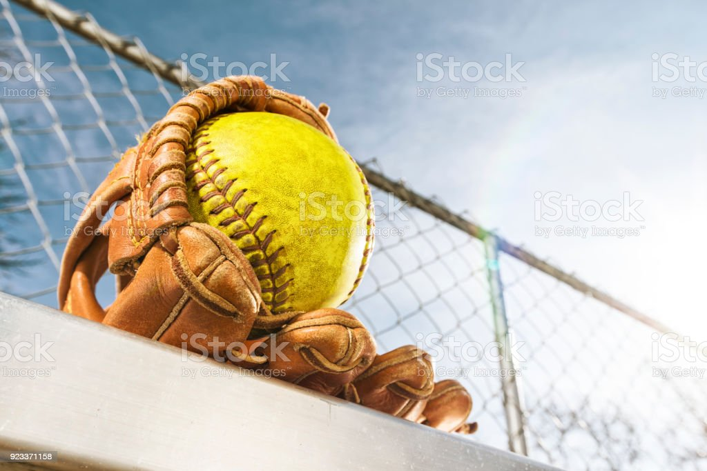 Looking up at a yellow softball in glove on bench with sun flare stock photo