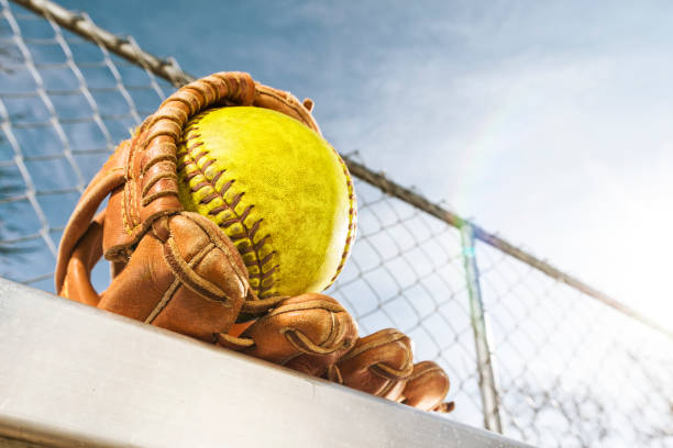 looking up at a yellow softball in glove on bench with sun flare - softball stock photos and pictures