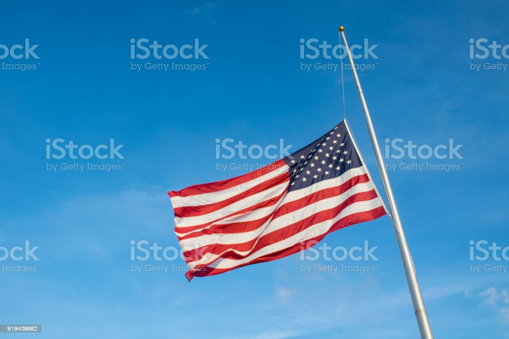 Looking up at American Flag waving in the wind at Half Mast after another School Shooting stock photo