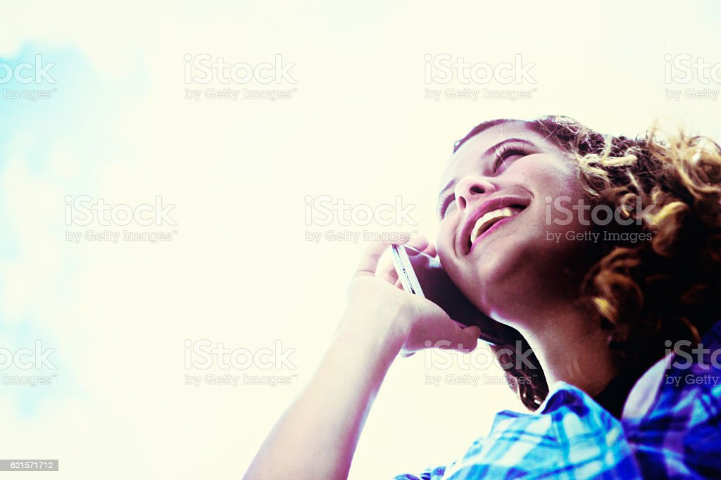 Looking up at beautiful girl using cellphone against bright sky photo libre de droits