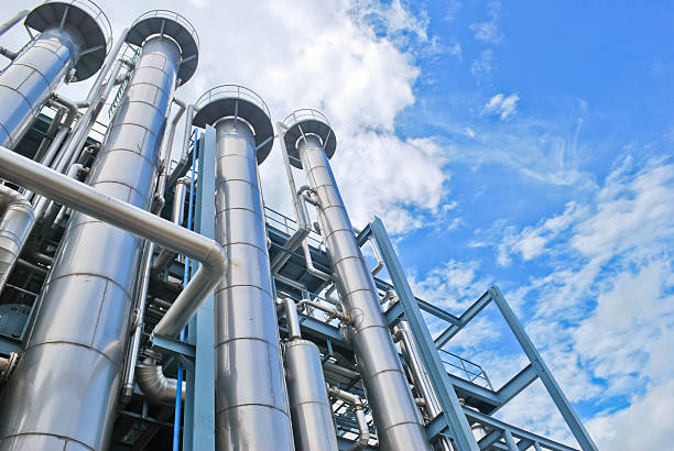 Looking up at chemical plant stacks Chemical plant against blue sky chemical plant stock pictures, royalty-free photos & images