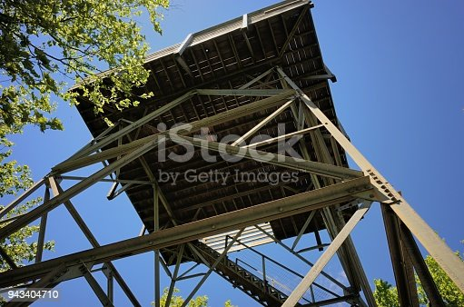 Close up looking up at bottom of metal and wooden firetower in woods